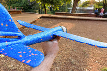 Closeup Of A Blue Styrofoam Plane With Orange Spots Being Held By Adult Hand.