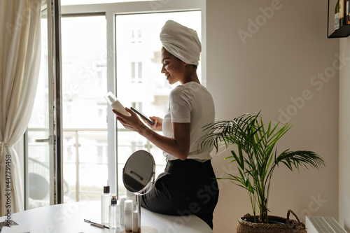 Murais de parede Woman in towel on head leans on white dressing table with mirror on it