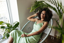 Dark-skinned Woman In Green Dress Sits On Chair. Curly Brunette Lady In Silk Outfit Relaxes In Armchair At Home.