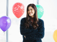 Asian Young Happy Woman In Furry Jacket Sitting In Front Gray Couch With Teddy Bear Dolls In Living Room Smiling Use Pencil Writing Name List On Orange Notebook While Wrapping Present Gift Boxes