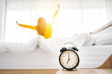 Good Morning New Day. Alarm Clock Wake Up And Woman Sitting Body Stretch On Bed Beside Window In Bedroom