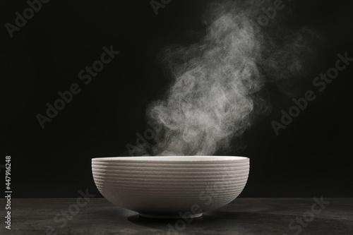 Obraz na plátně Steaming ceramic bowl on grey table against dark background