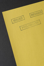 The Words Issued, Revised, And Preliminary Stamped In Dark Ink On Yellow Construction Paper