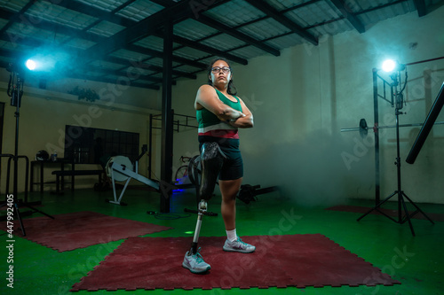 Fotografia Mexican woman athlete posing with prosthetic leg in gym