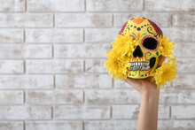 Hand With Painted Human Skull For Mexico's Day Of The Dead (El Dia De Muertos) And Flowers On Brick Background