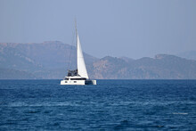 One-masted Sailing Yacht In The Sea. White Sailboat On Misty Mountains Background