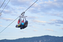 Unrecognizable People On Zip Line Over Mountains