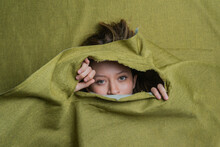 Young Woman Peeking Out Of Green Ripped Fabric