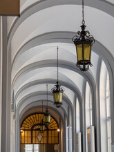 Antique And Huge Iron And Glass Chandeliers In A Public Corridor With Large Windows