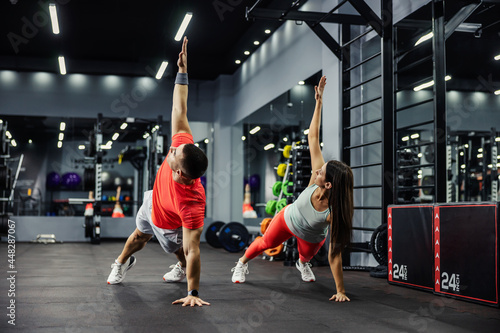 Photo The fitness man and energetic woman are in a plank position with their arms raised and doing full-body in a modern gym