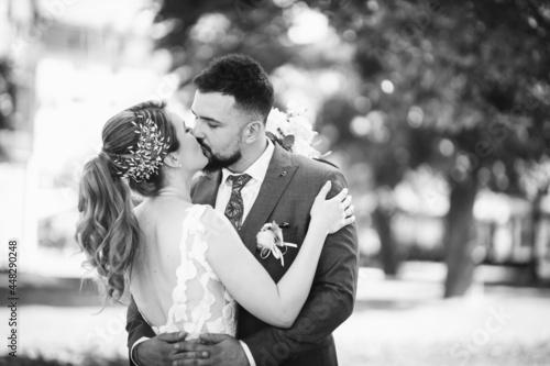 Billede på lærred Vgrayscale shot of a caucasian bride and groom on the wedding day outdoors