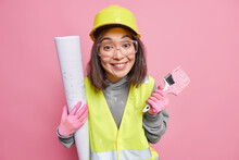 Indoor Shot Of Glad Female Builder Busy With House Renovation Holds Painting Brush And Building Blueprint Wears Uniform Isolated Over Pink Background. House Remodeling And Reconstruction Concept