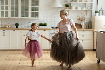 Happy little girl with mature grandmother wearing princess skirts dresses having fun standing in kitchen at home, smiling senior woman with adorable granddaughter enjoying leisure time together