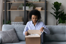 Happy Millennial African American Female Buyer Client Open Unpack Box With Internet Order, Buy On Web. Smiling Young Biracial Woman Unbox Package Shop Online From Home. Shipment, Delivery Concept.