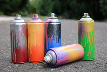 Used Cans Of Spray Paint On Asphalt Road. Graffiti Supplies
