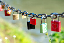 Red Padlock Suspended On A Chain Engraved With One Heart.