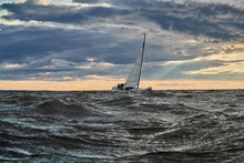 The Lonely Sailboat On The Horizon In Sea At Sunset, The Storm Sky Of Different Colors, Big Waves, Sail Regatta, Cloudy Weather, Only Main Sail, Sun Beams
