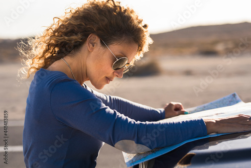Fototapeta Adult woman looking paper travel road trip map on the car outside with landscape