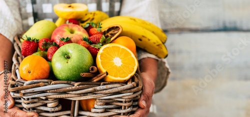Obraz na plátně Close up of tasty fresh fruits bucket holded by woman hands and copy space backg
