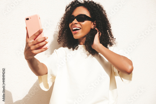 Beautiful black woman with afro curls hairstyle.Smiling hipster model in white t-shirt. Sexy carefree female posing in the street near white wall in sunglasses. Cheerful and happy.Taking selfie photo