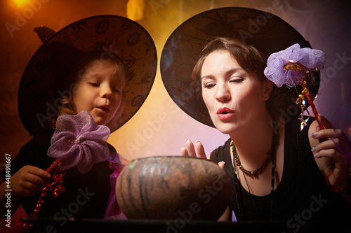 Canvas Beautiful brunette mother and cute little daughter looking as witches in special dresses and hats conjuring with a pot in room decorated for Halloween