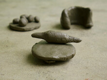 Mud Soil Crafted Cooking Food Toys Presented On Cemented Field.