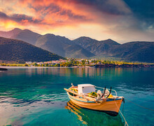 Colorful Sunrise In Logari Port With Small Fishing Boat With Kyparissi Village On Background. Picturesque Summer Scene Of Peloponnese Peninsula, Greece, Europe. Calm Morning Seascape Of Myrtoan Sea.