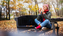 Young Adult Happy Woman 40 Years Old In Bright Clothes Sits In An Autumn Park With A Yellow Leaf In Her Hands