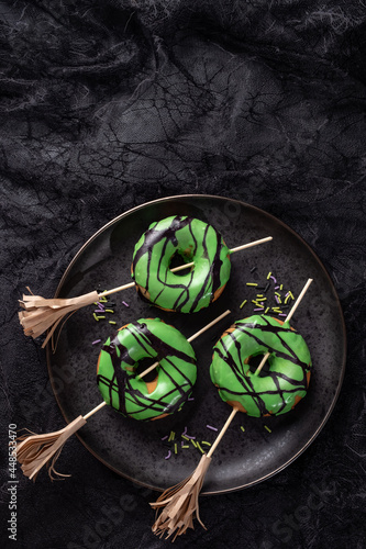 Halloween donut with green glaze and witch's broom. Halloween trick or treat.