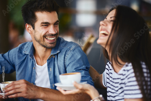 Man and women drinking coffee in a summer cafe