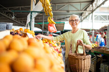 Portrait Of Senior Caucasian Woman Buying Fresh Organic Vegetables And Fruit At Market Place And Holding Bag Full Of Healthy Food.