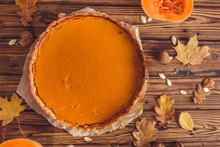 Orange Spicy Autumn Pumpkin Pie. Shortcrust Vanilla Tart With Sweet Pumpkin Cream On Brown Wooden Background With Small Sliced Pumpkins Walnuts Oak Leaves And Seeds. Free Copy Space. Top View