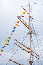Ship's Mast With Colorful Pennants Against The Sky