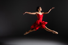 Side View Of Ballerina In Red Dress Jumping On Black Background