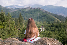 Little Beautiful Girl Portrait With Long Hairs In Traditional Mountain Region Dress - Red Skirt. Small Toddler Girl Outside In The Mountains With Summer Flowers Bouquet And Breathtaking View
