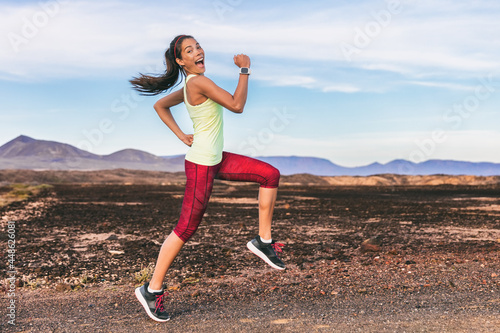 Fototapeta Fun fitness workout personal trainer athlete woman happy goofy jumping to motivate running
