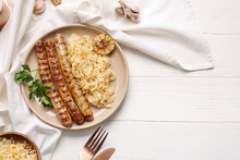 Plate With Tasty Sauerkraut And Grilled Sausages On Light Wooden Background