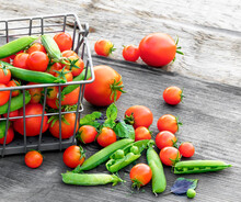 Tomatoes And Green Peas In Metal Basket On Wooden Rustik Table.