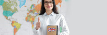 Young Woman In Glasses Holds Thumb Up And Notebook With English