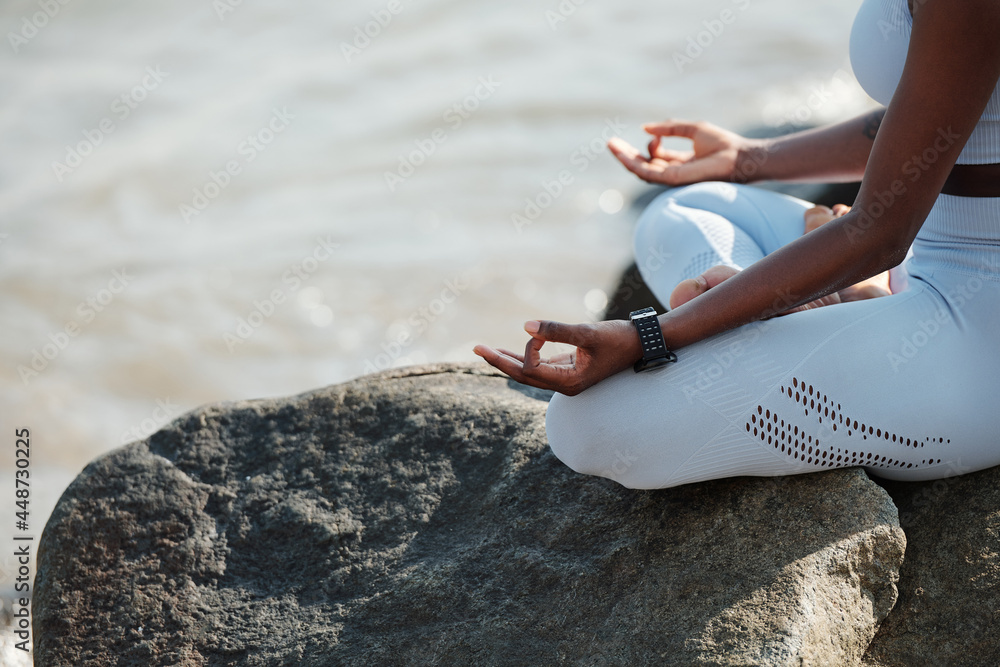 Obraz Close-up image of fit woman sitting in lotus position enjoying her calm meditation in beach fototapeta, plakat