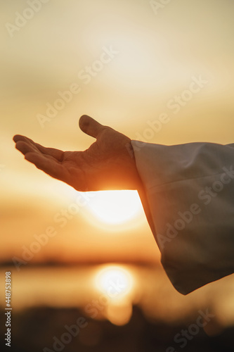 Jesus Christ reaching out his hand at sunset. Fotobehang
