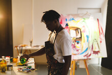 African American Male Painter At Work Holding Paint In Art Studio
