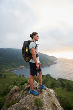 Male Hiker Standing On Rock Above Sea