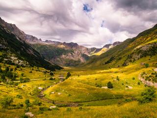 Panorámica de un valle de alta montaña en el que se aprecian verdes pastos, montañas y nubes.
