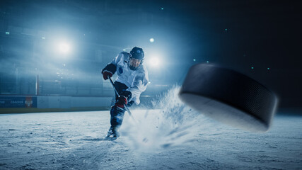 Ice Hockey Rink Arena: Professional Player Shooting the Puck with Hockey Stick. Focus on 3D Flying Puck with Blur Motion Effect. Dramatic Wide Shot, Cinematic Lighting.