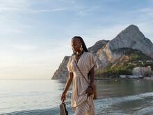 Black Female Tourist Walking Near Waving Sea At Sunrise