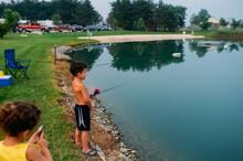 Boy Standing Near The Edge Of Pond Fishing.