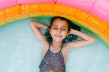Kid Relaxing Inside Inflatable Colorful Swimming Pool