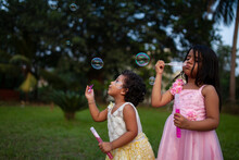 Little Indian Girls Playing With Soap Bubbles In A Park