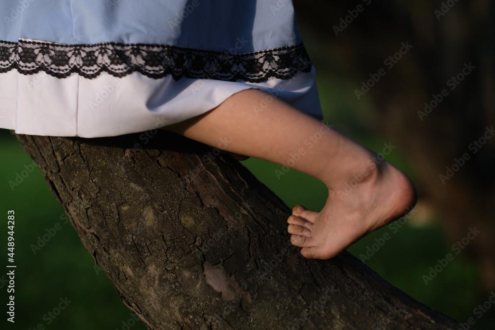 bare feet of a child climbing a tree. happy childhood concept. Montessori education